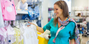 Best infant baby clothing gift sets-Lady in baby shop selecting baby clothes.