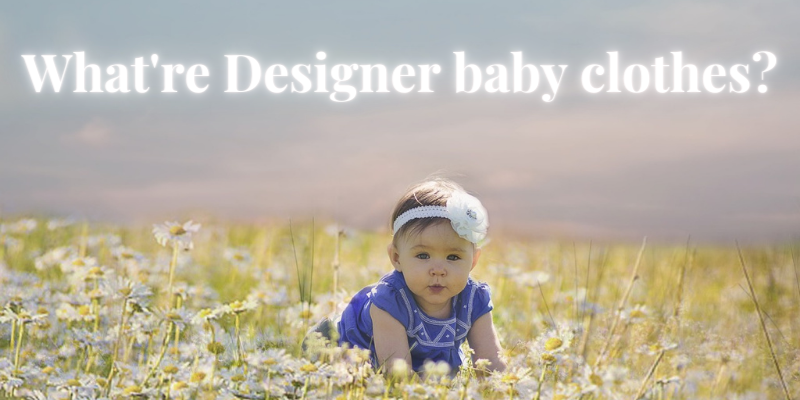 What're designer baby clothes brands that are affordable?-Baby girl with white headband outside in nature.