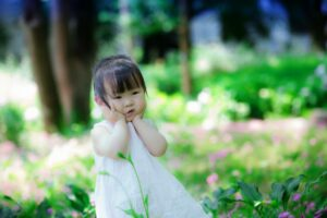 What're designer baby clothes?-Baby girl wearing a white dress.