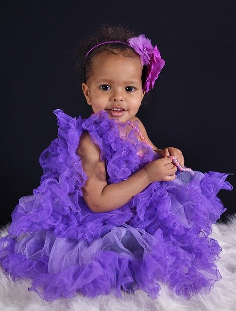What're Designer baby clothes?-Little girl dressed up in a purple dress.