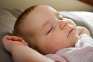 Affordable organic baby clothes in Australia-Sleeping Newborn baby wearing white with pink stripped outfits.